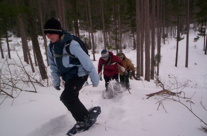 students going up hill in snowshoes