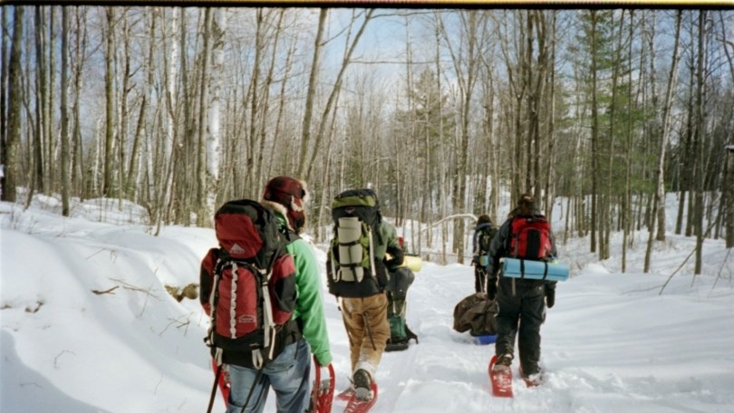 students snowshoeing on winter trail