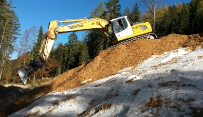 Snow farming. Snow is buried from the previous season in a hole in the forest then covered by wood-chips. Photo credit: Olympiaregion Seefeld.