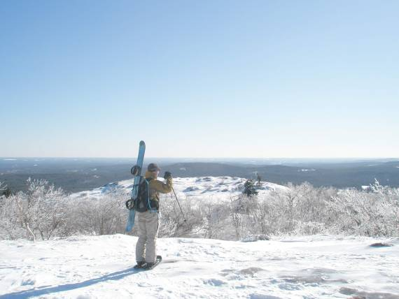 man with snowboard strapped to pack in the backcountry