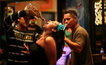 Pouring alcohol into someone's mouth