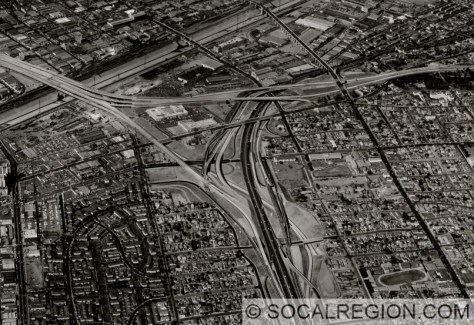 Oblique aerial view of the East Los Angeles Interchange. Taken by the Division of Highways on October 30, 1961. Connections to SR-60 have been built but aren't in use. They won't be until 1965. The ramps to I-10 opened in 1962.