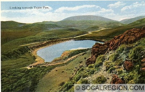 This postcard of the old Ridge Route in Peace Valley shows not only a great example of a fault scarp, but also shows a sag pond adjacent to the scarp. The large mountain visible in the distance is Frazier Mountain. The fault runs through the valley visible on the right side of the mountain.