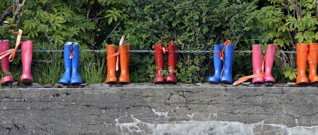 rain boots on a fence