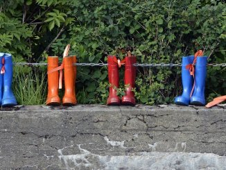 rain boots on a fence
