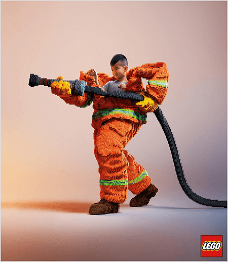 This is a photo from a LEGO ad that shows a young Asian boy inside a firefighter uniform made of LEGOs. The uniform is orange with a neon green stripe around the cuffs of the coat and pants. The firefighter is standing with one foot back and holding a firehose, also made of legos. The boy's head appears out of the top of the uniform, which is much larger than he is and stops around the shoulders. The photo was taken against a plain neutral background. The LEGO logo appears in a red box in the lower right. Talia Wolf says LEGO is a great example of a brand that uses emotion in advertising.