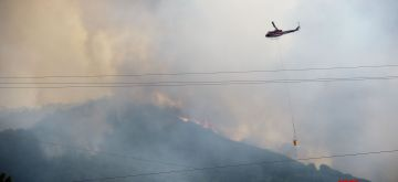 NAPA VALLEY (U.S.), Oct. 11, 2017 (Xinhua) -- A helicopter tries to put out the wildfire in California's Napa, the United States, on Oct. 10, 2017. The death toll has risen to 15 in north California wildfires as more casualties were confirmed Tuesday in several counties near San Francisco in western California in west United States. (Xinhua/Wu Xiaoling/IANS)