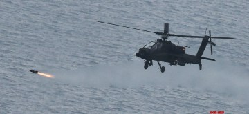In this photo released by the Army, an Apache attack helicopter launches a Hellfire air-to-surface missile toward the Jik Islet bombing range off Gunsan on South Korea's western coast on Nov. 13, as the South Korean Army carries out its first live-fire exercise involving the firing of Hellfire air-to-surface missiles in a bid to beef up its capability to fight in the air. (Yonhap/IANS)