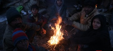 Srinagar: People sit around the fire to warm themselves on a cold day at Jammu Srinagar National Highway, on Dec 10, 2018. (Photo: IANS)