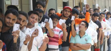 New Delhi: People show their voter identity card at a polling booth during the sixth phase of 2019 Lok Sabha elections, in New Delhi on May 12, 2019. (Photo: IANS)