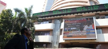 As Finance Minister P. Chidambaram presents the General Budget in Parliament, investors monitor the stock market on the giant screen in front of Bombay Stock Exchange building  in Mumbai on Feb. 28, 2013. (Photo: Sandeep Mahankal/ IANS)