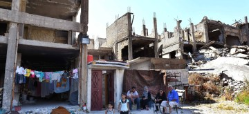 """HOMS, June 11, 2019 (Xinhua) -- The Shtaiwi family sits outside their house amid the rubbles in the Wadi al-Sayeh street in the central city of Homs, Syria, May 29, 2019. Kamal Shtaiwi, 58, enjoys returning to his home with his wife and four children, even though it is surrounded by the destruction of war. TO GO WITH Feature: Displaced Syrian family back """"home, sweet home"""" amid rubble (Xinhua/Ammar Safarjalani/IANS)"""