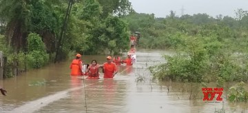 Valsad (Gujarat): NDRF personnel evacuate people from houses in low lying areas of Salvav village in Gujarat's Valsad district after heavy rains resulted in a flood-like situation in the district, on July 8, 2019. (Photo: IANS/NDRF)