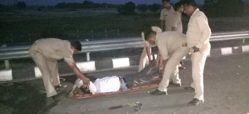 Kannauj: Police personnel take an injured to the hospital in Uttar Pradesh's Kannauj district on June 11, 2018. Seven students were killed and two others critically injured on Monday after they run over by a bus in Uttar Pradesh's Kannauj district. The accident took place on the Agra-Lucknow Expressway when one of the buses broke down after it ran out of fuel following which the nine students came out and were strolling on the roadside. (Photo: IANS)