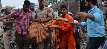 Gurdaspur: A body being retrieved from the site of a blast at an unauthorized firecracker factory in a residential in Batala town of Punjab's Gurdaspur district on Sep 4, 2019. At least 19 people were killed and more than 25 injured in the blast. (Photo: IANS)