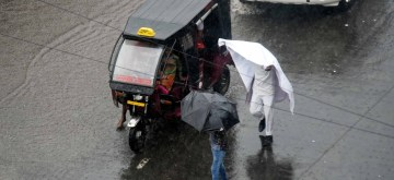Patna: People shield themselves during rains in Patna on Sep 13, 2019. (Photo: IANS)