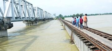 Darbhanga: People walk across a railway bridge over the swollen Bagmati river following incessant monsoon rainfall, in Bihar's Darbhanga district on July 31, 2019. (Photo: IANS)