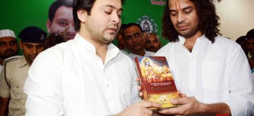 Patna: RJD leader Tej Pratap Yadav gifts a copy of Shrimad Bhagwat Geeta to his brother Tejashwi Yadav on his birthday, in Patna on Nov 9, 2019. (Photo: IANS)