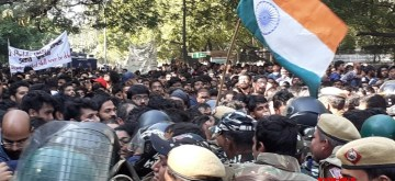 New Delhi: JNU students being stopped by the police from continuing with their protest march to Parliament by putting up barricades, in New Delhi on Nov 18, 2019. Police erected barricades a kilometre away from Parliament to prevent the students from proceeding, leading to students trying to climb over the barricades. The protest march is against the hostel fee hike. (Photo: IANS)