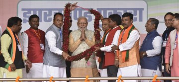 Khunti: Prime Minister Narendra Modi being welcomed by BJP's candidates from Hatia and Ranchi Assembly seats, Navin Jaiswal and CP Singh respectively during a public meeting ahead of the second phase of Jharkhand Assembly elections, in Khunti district on Dec 3, 2019. (Photo: IANS)