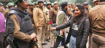 Demonstrators give flowers to police.