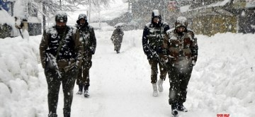 Baramulla: Army personnel walk through a snow-covered street during heavy snowfall in Jammu and Kashmir's Baramulla on Jan 13, 2020. (Photo: IANS)