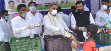 Bengaluru: Congress leader Siddaramaiah distributes food and water among the poor, needy and homeless people during the 21-day nationwide lockdown (that entered the 16th day) imposed as a precautionary measure to contain the spread of coronavirus, in Bengaluru on Apr 9, 2020. (Photo: IANS)