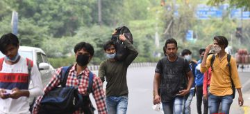 New Delhi: Migrant labourers from Uttar Pradesh walking on foot in a bid to reach their home towns at Delhi's Rajghat during the extended nationwide lockdown imposed to mitigate the spread of coronavirus, on May 14, 2020. (Photo: IANS)