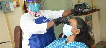 Mumbai: A beautician attends to a customer at a beauty parlour wearing mask, face shield and Personal Protective Equipment (PPE) suit as a precautionary measure against COVID-19 after barber shops, salons and beauty parlours were allowed to resume operations by the Maharashtra Government as part of the state's unlocking process amid coronavirus pandemic, in Mumbai on June 28, 2020. The State government is likely to make more announcements relaxing restrictions on various economic activities, as the ongoing phase of the lockdown will end on June 30. (Photo: IANS)