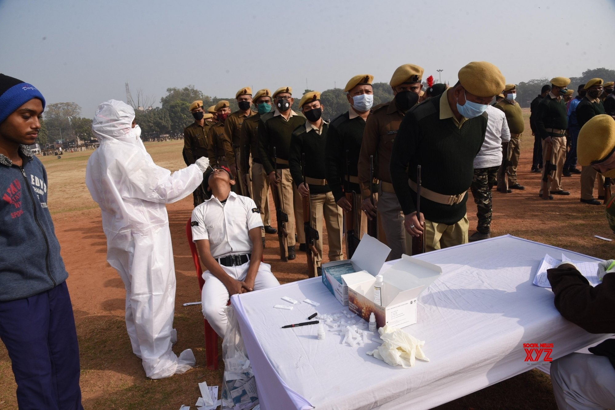 Patna: - A health worker collects sample from a security personnel for COVID - 19 test, before republic day parade rehearsal at Gandhi Maidan in Patna #Gallery