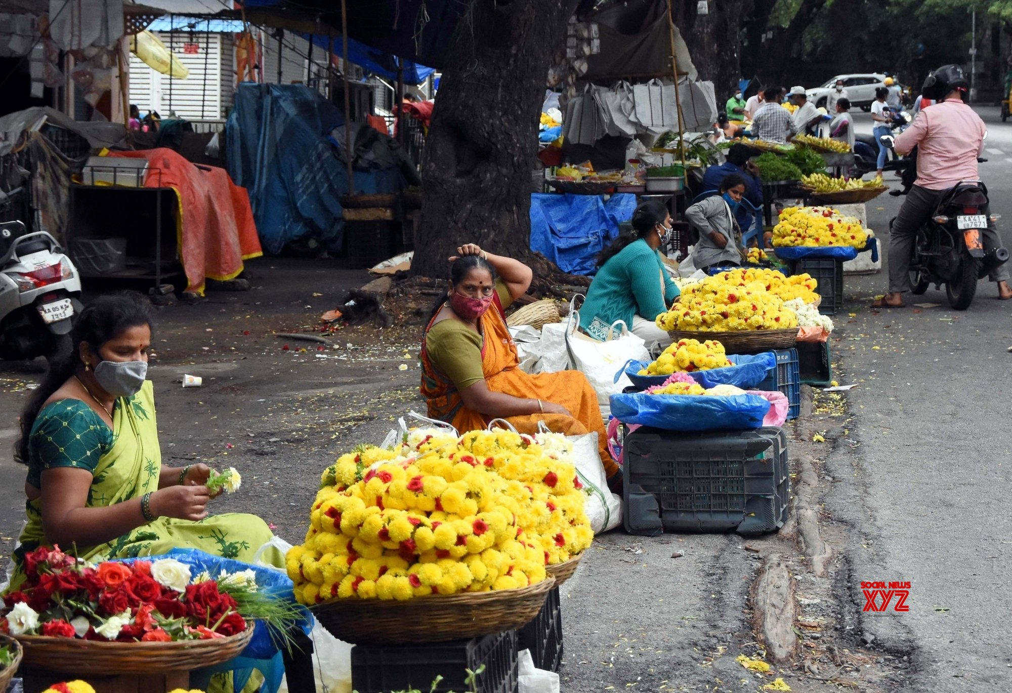 Bengaluru : Flower vendors waiting for the customers at Gandhi Bazaar during Coronavirus lockdown in the wake of the 2nd wave of COVID - 19, in Bengaluru. #Gallery