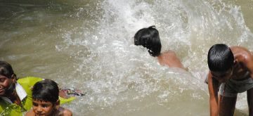 New Delhi:  Children enjoying in water pond during hot weather in New Delhi on Thursday 10 June 2021. (Photo: Qamar Sibtain/ IANS)
