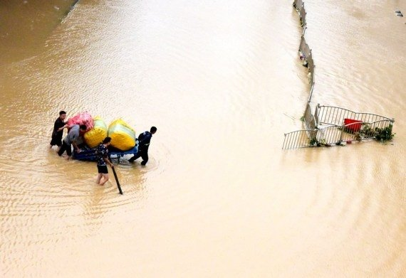 Citizens transport their property on a flooded street in Zhengzhou, central China's Henan Province, July 21, 2021. #Gallery