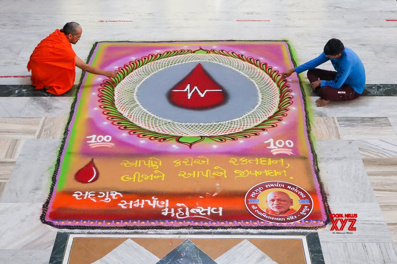 : Ahmedabad :Swaminarayan saints and others give final touches to 1410 ft Rangoli on the theme of Donate blood, save life at a Kumkum Swaminarayan temple Source : AD SS #Gallery