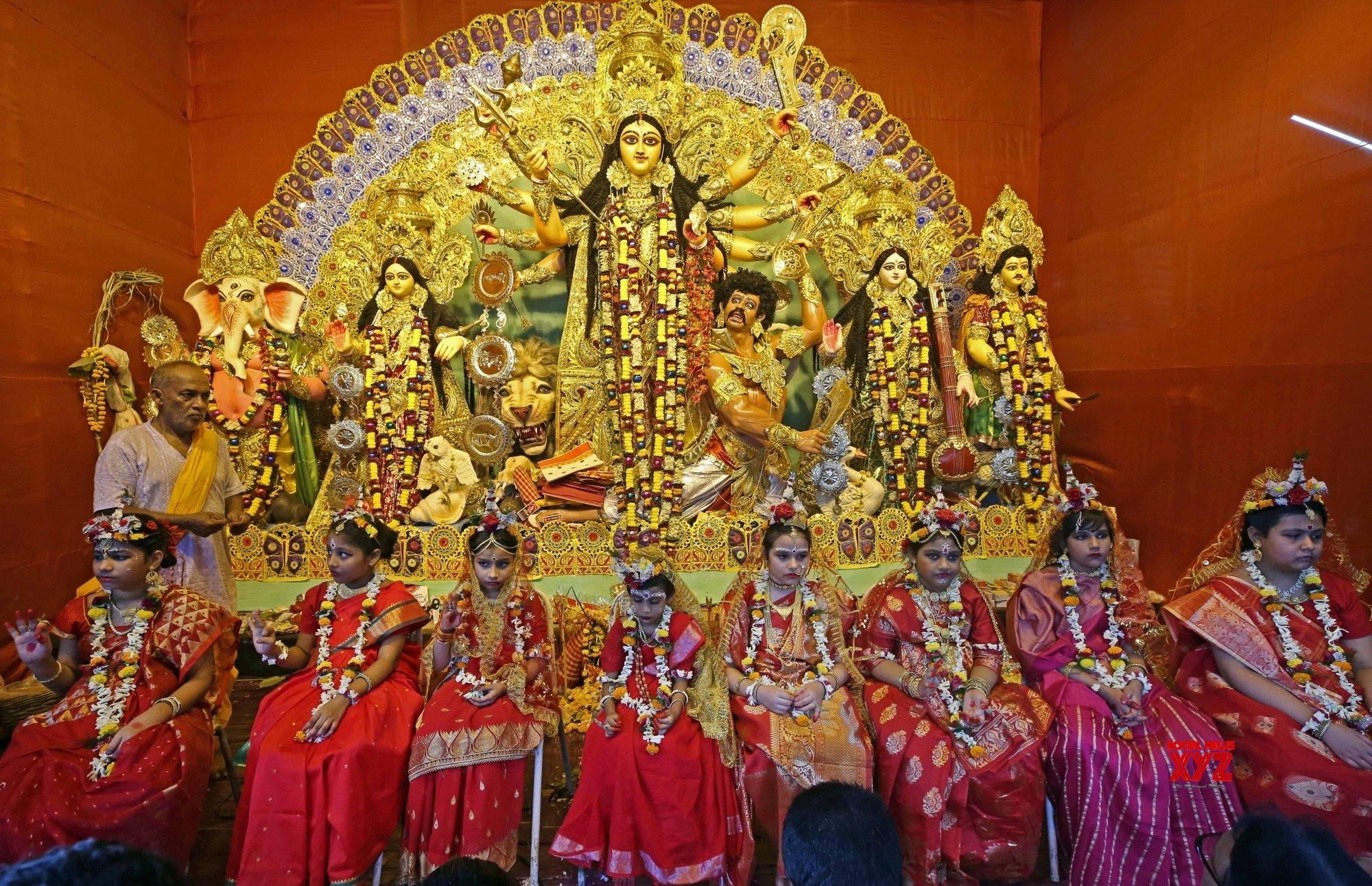 Kolkata : Hindu priests guide a young unmarried girls known as 'Kumari', who dress up as the Hindu goddess Durga on Maha Ashtami Puja, during a ritual for the Durga Puja festival at a community puja pandal in Kolkata #Gallery