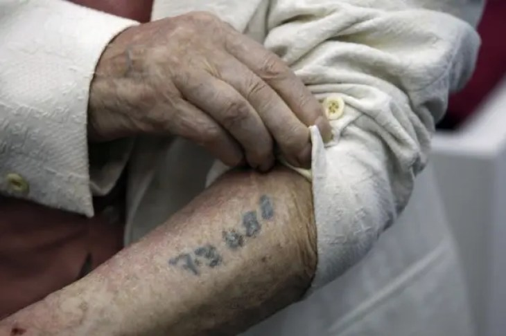 Polish-born Holocaust survivor Meyer Hack shows his prisoner number tattooed on his arm during a news conference at the Yad Vashem Holocaust Museum in Jerusalem June 15, 2009. A 95-year-old Auschwitz survivor, Hack, donated jewellery he took from the clothing of Jews who were gassed to death at the Nazi camp to Yad Vashem on Monday. Hack, who now lives in Boston, found the gems while sorting the clothing of victims sent to die in the gas chambers, which was his job at the camp where his mother, brother and two sisters perished. REUTERS/Baz Ratner (JERUSALEM CONFLICT SOCIETY) - RTR24OVC