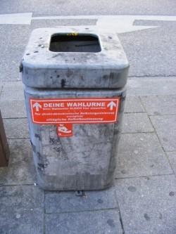 """Foto: Abfallbehälter mit Aufkleber """"Deine Wahlurne – Bitte Wahlzettel gleich hier einwerfen [...]"""" / Mattes / CC BY-SA 3.0"""