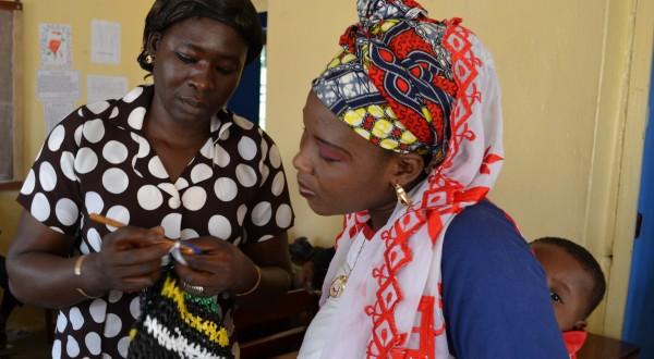 Odile Sannou, Workshopleiterin aus Benin, erklärt Baraka Oukpedjou aus Sokodé, wie sie den Henkel häkeln soll - Plastikmüll