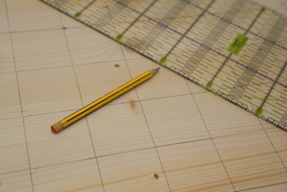 Löcher im Abstand von 5 cm auf Holzbrett anzeichnen.  Garnrollenhalter selber bauen