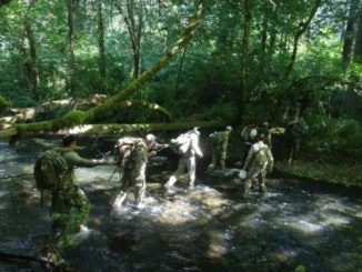 """Members of 1st Special Forces Group conduct a stream crossing during the 60th Anniversary """"Living History Training Event"""" held June 2017 (Photo MAJ Alexandra Weiskopf, 1st SFGA)"""