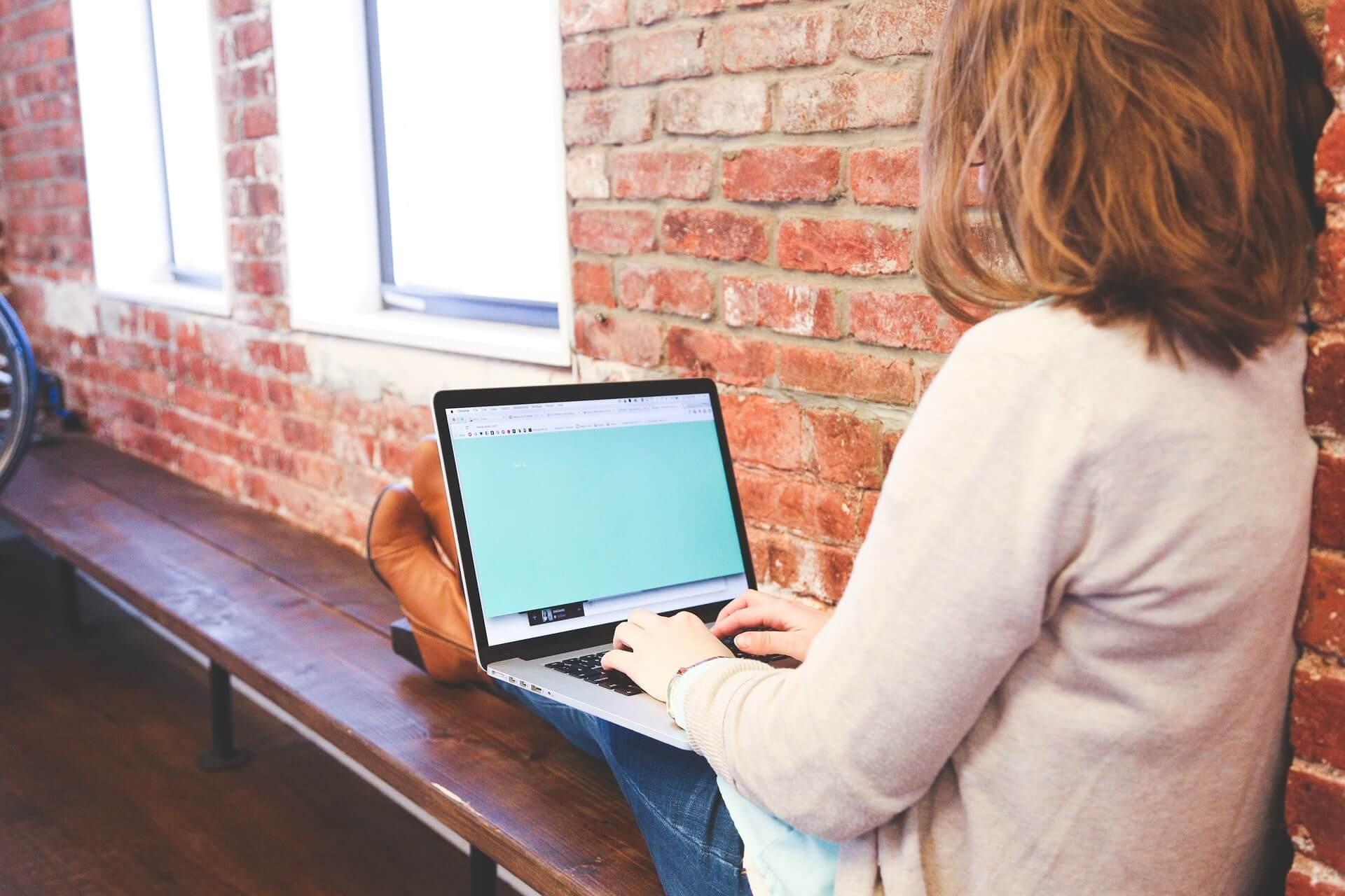 Eine Frau sitzt auf einer Fensterbank und tippt am Laptop