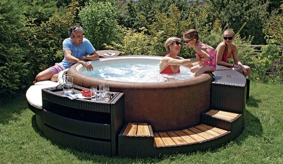 Spa Softub, spa dur sur lequel une famille joue avec une petit fille assise sur le spa