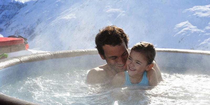 Une petite fille et son père dans un spa softub en pleine montagne