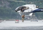 Soldier holding a dog jumping from a helicopter over a lake