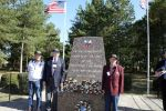 World War II vets standing by a memorial