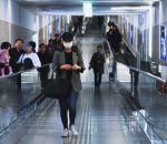 Woman walking down a hall with a medical mask on