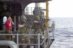 Soldiers pointing guns off a boat
