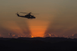 Picture of a military helicopter in the sky with an orange sunset. Picture for decorative purposes only.