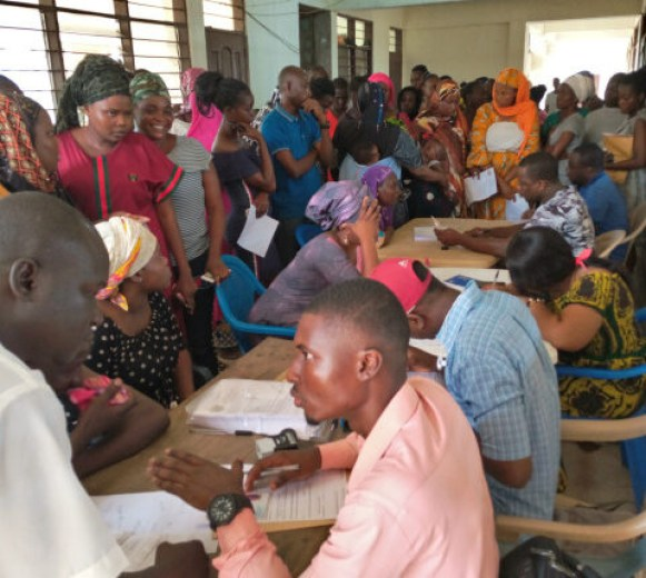 A section of Ghanaians in cue to register for the Ghana Card in Eastern Region
