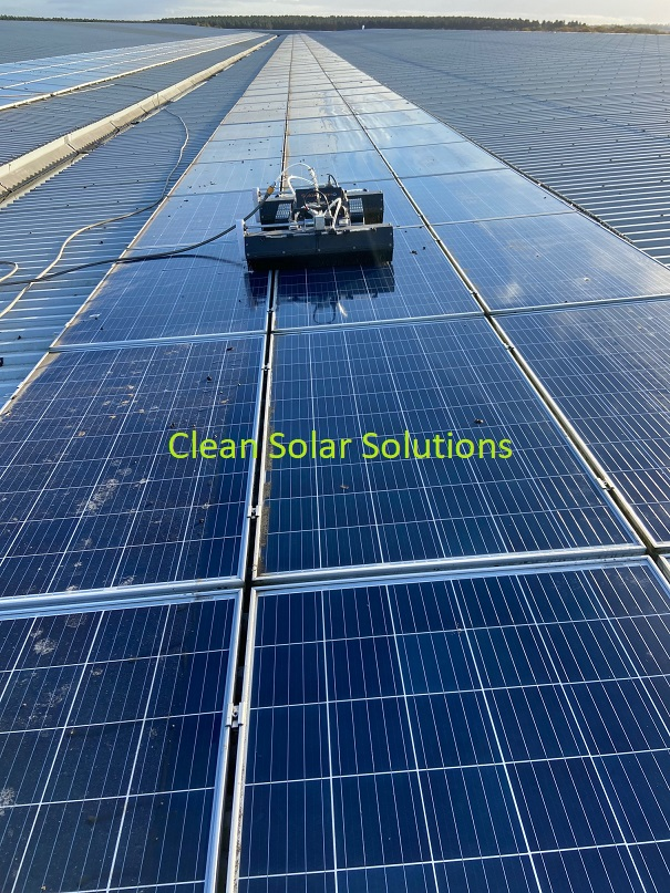 Roof mounted solar panels being cleaned with a robot